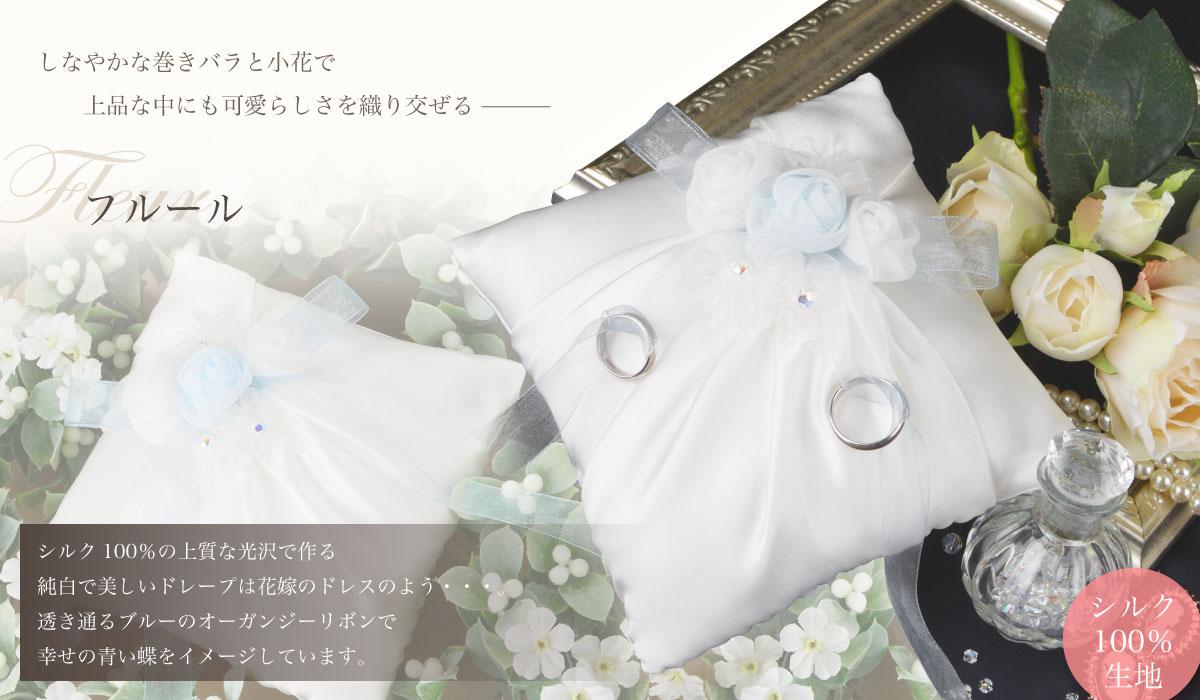 しなやかな巻きバラと小花で、上品な中にも可愛らしさを織り交ぜる「フルール」シルク100%の上質な光沢で作る純白で美しいドレープは花嫁のドレスのよう・・・。透き通るブルーのオーガンジーリボンで幸せの青い蝶をイメージしています。