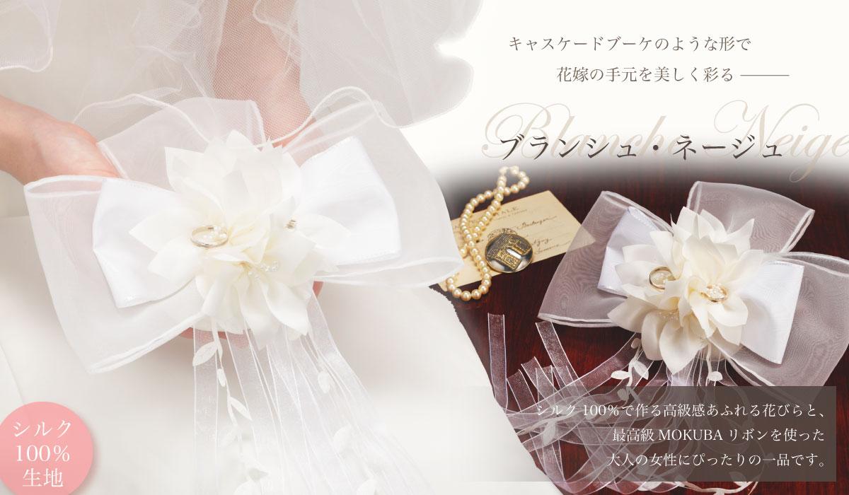 キャスケードブーケのような形で、花嫁の手元を美しく彩る「ブランシュ・ネージュ」シルク100%で作る高級感あふれる花びらと、最高級MOKUBAリボンを使った大人の女性にぴったりの一品です。