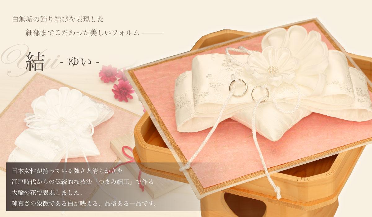 白無垢の飾り結びを表現した、細部までこだわった美しいフォルム「結 -ゆい-」日本女性が持っている強さと清らかさを江戸時代からの伝統的な技法「つまみ細工」で作る大輪の花で表現しました。純真さの象徴である白が映える、品格ある一品です。